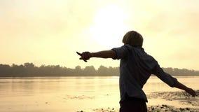 De jonge Mens werpt Zijn Hand vooruit, opheft beiden, geniet van het Leven, in slo-Mo stock videobeelden