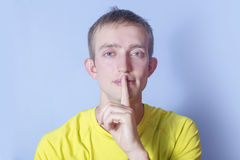 De jonge mens zette een vinger aan zijn lippen Eindebespreking! Royalty-vrije Stock Foto