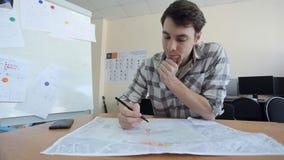De jonge mens zit bij houten lijst en creeert blauwdruk stock footage
