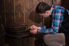 De jonge mens zit dichtbij een vat en het proberen om op te lossen een raadsel aan stock afbeeldingen