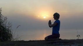 De jonge mens zit en bidt op een meerbank bij zonsondergang in slo-mo stock video