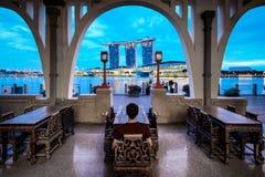 De jonge mens zit en geniet van de mening van het zand van de jachthavenbaai, Singapore royalty-vrije stock foto