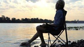 De jonge Mens zit en glimlacht en beweegt Zijn Blootvoets in Water op een Riverbank stock video