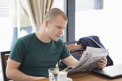 De jonge mens zit en leest nieuw nieuws in dagelijkse kranten royalty-vrije stock foto