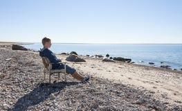De jonge mens zit en ontspant op stoel bij strand Royalty-vrije Stock Foto's