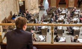 De jonge mens zit in galerij en let op wetgevende werkzaamheden stock foto's