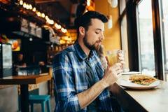 De jonge mens zit in het restaurant en proeft een warme drank royalty-vrije stock fotografie