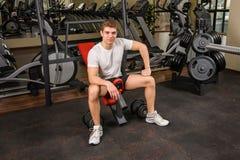 De jonge mens zit na training in gymnastiek Stock Afbeeldingen