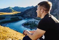 De jonge mens zit op de bovenkant van nountain met panoranic mening van de bergrivier en onderzoekt de afstand royalty-vrije stock foto's
