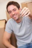 De jonge mens zit op de vloer houdend een sleutel Stock Afbeeldingen