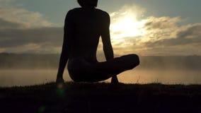 De jonge mens zit op een meerbank en een praktijkenyoga bij zonsondergang in langzame motie stock video