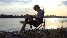 De jonge Mens zit op een Stoel en schrijft Zijn Meesterwerk op een Riverbank stock footage