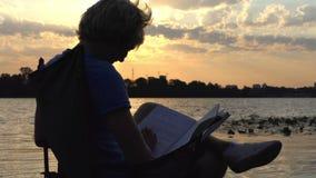 De jonge Mens zit op een Vouwende Stoel op Riverbank, leest bij Zonsondergang stock videobeelden