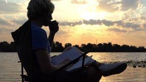 De jonge Mens zit op een Vouwende Stoel op Riverbank, leest Zijn Nota's bij Zonsondergang stock videobeelden