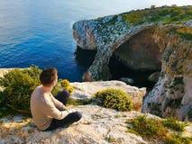 De jonge mens zit op de rand van een klip en bewondert het overzees en de stenen royalty-vrije stock foto's
