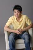 De jonge mens zit op stoel Stock Foto