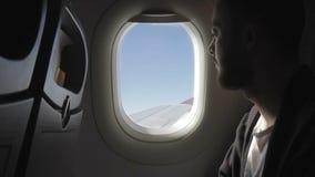 De jonge mens zit op vliegtuig en kijkt uit venster zorgvuldig stock video