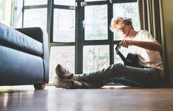 De jonge mens zit thuis op de vloer en stemt de gitaar royalty-vrije stock foto