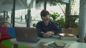 De jonge mens zoekt informatie in het boek in de bibliotheek stock videobeelden