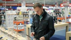 De jonge mens in zwart leerjasje kiest een nieuwe mobiele telefoon in een winkel, controlerend hoe het werkt stock footage