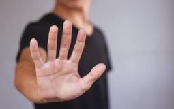 De jonge mens in zwarte t-shirt toont zijn hand Stock Afbeelding