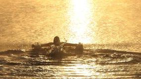 De jonge mens zwemt vlinder in een meer bij verbazende zonsondergang in slo-mo stock video
