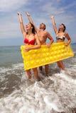 De jonge mensen hebben pret op zeekust en greep mattres Royalty-vrije Stock Foto's
