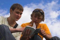 De jonge mensen lezen het boek Stock Foto's