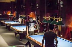 De jonge mensen spelen biljart royalty-vrije stock foto's