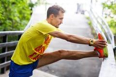De jonge mensen voert zich het uitrekken vóór jogging uit Stock Afbeeldingen