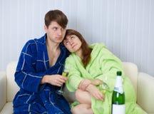 De jonge mensen zitten thuis op laag met fizz stock foto's