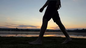 De jonge mensenbenen gaan langs een meer bij een schitterende zonsondergang in slo-mo stock videobeelden