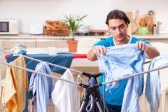 De jonge mensenechtgenoot die kleding doen die thuis strijken stock afbeeldingen