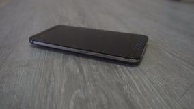 De jonge mensenhand neemt mobiele telefoon van grijze achtergrond stock video