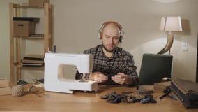 De jonge mensenhoofdtelefoons en luistert aan muziek Het werken als kleermaker en het gebruiken van een naaimachine in een textie stock videobeelden
