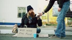 De jonge mensenhulp aan dakloze persoon en het geven van hem wat voedsel terwijl de alcohol van de bedelaarsdrank en zit dichtbij Stock Fotografie