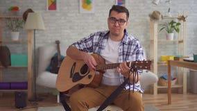 De jonge mensenmusicus met glazen kan geen gitaar spelen stock footage