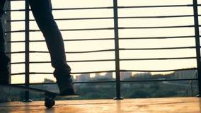 De jonge mensenritten op twee rijden wielen, langzame motie met een skateboard stock footage