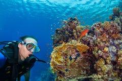 De jonge mensenscuba-uitrusting duikt onderzoekend koraalrif royalty-vrije stock fotografie
