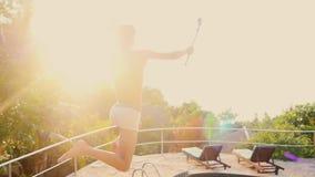 De jonge mensensprongen met gaan procamera in zwembadwater bij Zonsondergang door de zon Langzame Motie 1920x1080 stock videobeelden