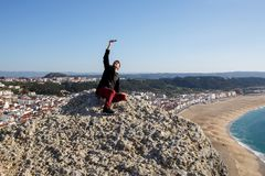 De jonge mensentoerist maakt selfie, hoog op de berg, op overzees strand op achtergrond Stock Afbeeldingen