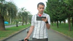De jonge mensentoerist is met een grote koffer op wielen rond het stadspark In de handen van een tablet met een tablet en is stock videobeelden