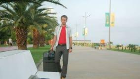 De jonge mensentoerist is met een grote koffer op wielen rond het stadspark Hij houdt rond op en kijkt Een mens in een wit stock videobeelden