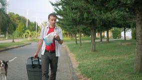 De jonge mensentoerist is met een grote koffer op wielen rond het stadspark In zijn handenkaart, en hij zoekt stock video