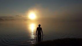 De jonge mensentribunes in een meer en bekijkt zonsondergang in slo-mo stock videobeelden