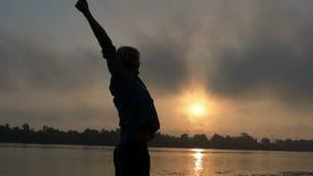 De jonge Mensentribunes op een Rivierbank, heft gelukkig Zijn Handen bij Zonsondergang in slo-Mo op stock video