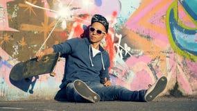 De jonge mensenzitting dichtbij een straatmuur werpt en vangt zijn skateboard stock footage