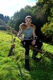 De jonge middeleeuwse schutter met kettingsoverhemd zit op tak in de aard in het zonlicht, drinkend hoorn in de hand, pijl en kro Stock Fotografie