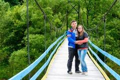 De jonge minnaars bevinden zich op een brug over een rivier dichtbij groene bomen stock foto