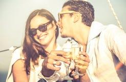 De jonge minnaars koppelen op zeilboot aan nadruk op het glastoejuiching van de champagnefluit - Gelukkig exclusief alternatief l royalty-vrije stock afbeeldingen